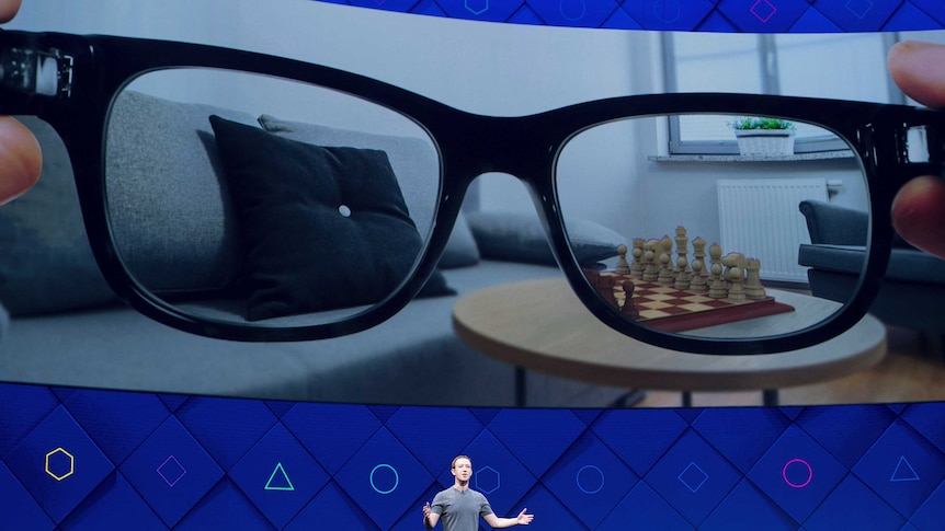 Mark Zuckerberg at F8 with augmented reality glasses on screen behind him