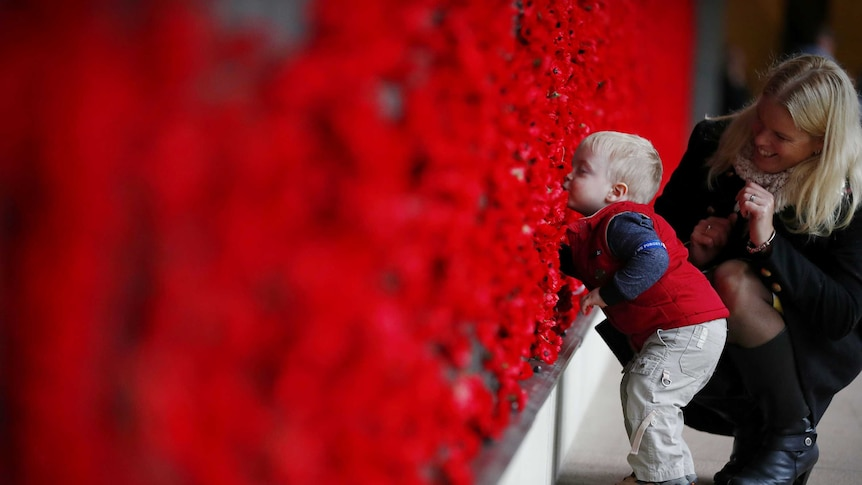 Naomi Laughton with 18-month-old Alexander Laughton place a poppy of the Roll of Honour after the Anzac Day dawn service