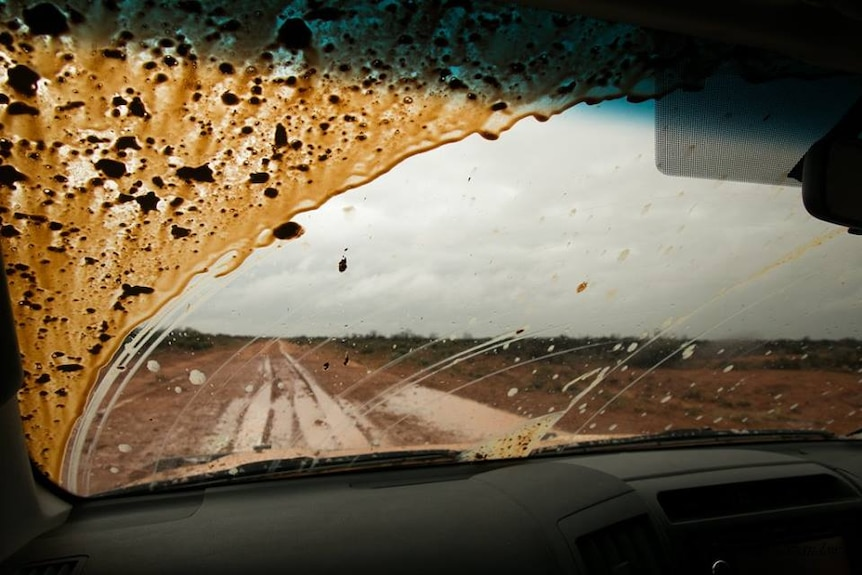 View from the dash of a car of a wet and muddy road in far west New South Wales.