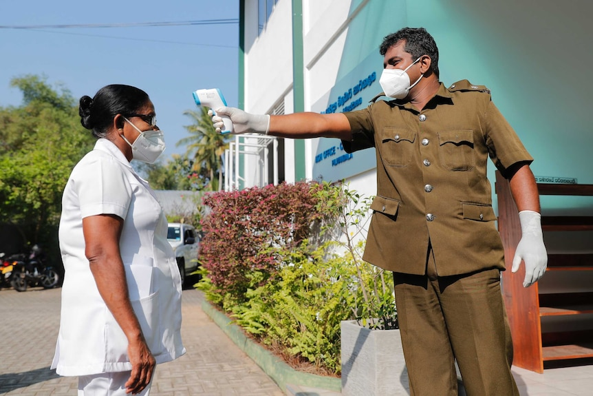 Masked man holds up laser thermometer to woman's forhead.