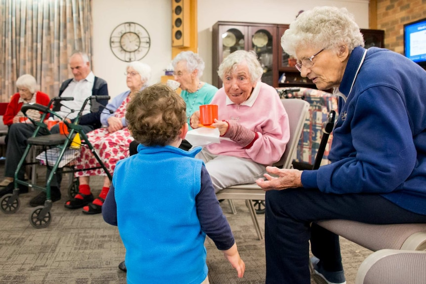 A toddler entertains residents in an aged care home