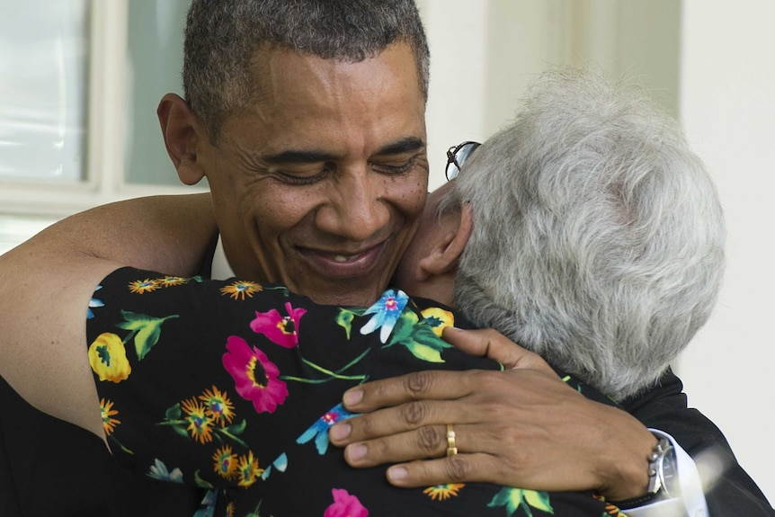 US President Barack Obama smiles as he hugs an older woman in a floral shirt.