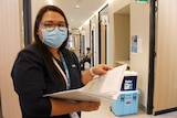 A young woman with a surgical mask and glasses looks up from a folder with two eskys in the background