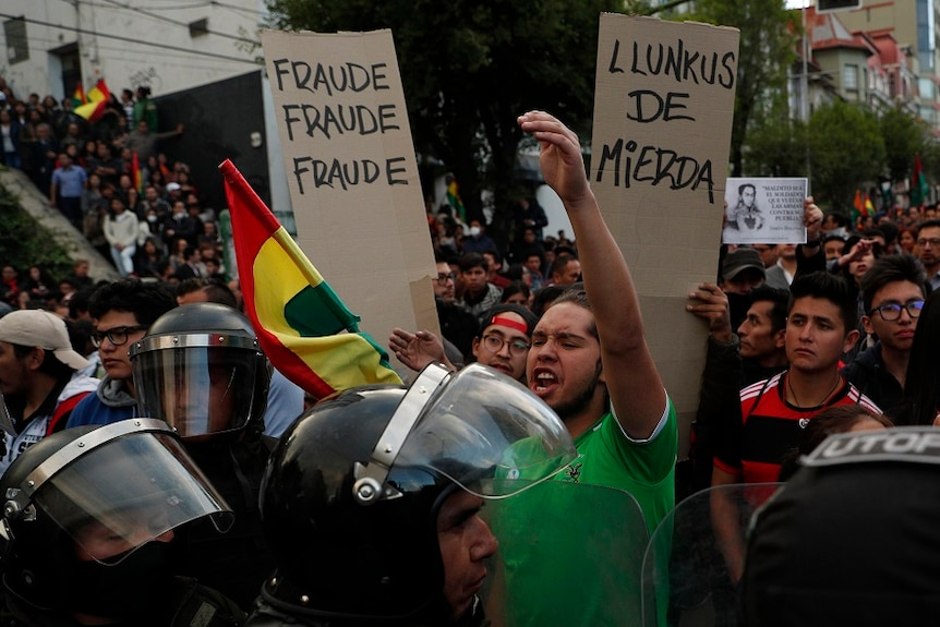 Protesters in the streets of Bolivia holidng up sign with Fraude written on them.