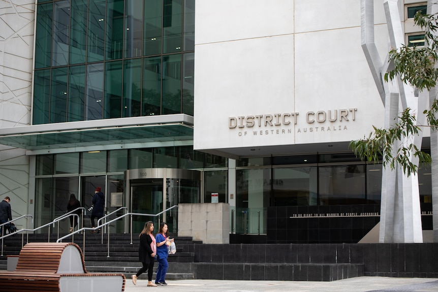 Two people walk past the entrance to WA's District Court.