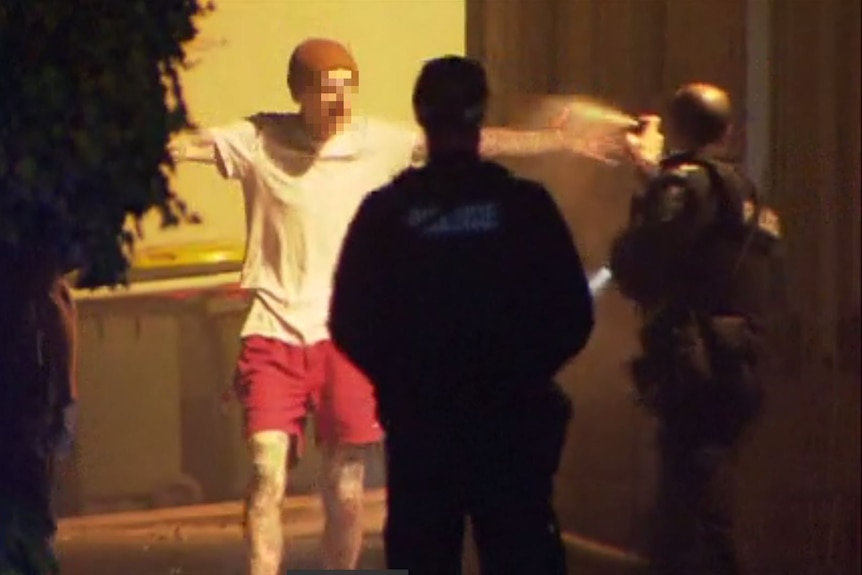 Two police officers spray at a man wearing a white shirt, red shorts and a beanie