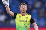 David Warner holds his helmet in the air and gestures to the crowd as he walks alongside Steve Smith