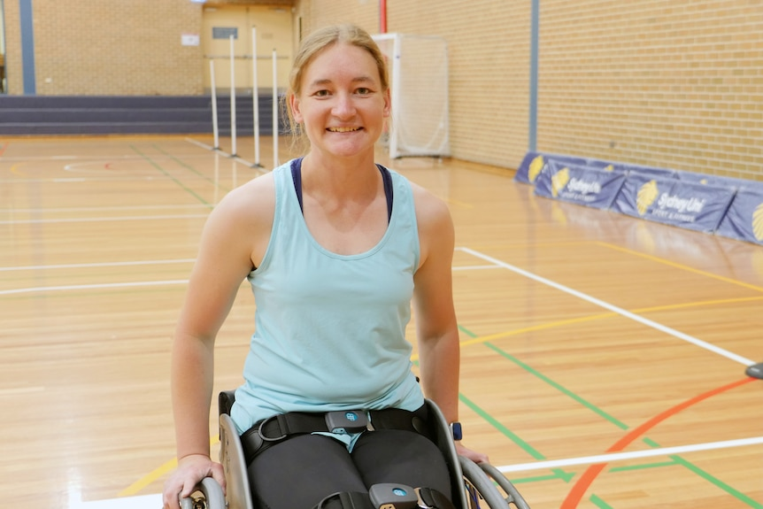 A wheelchair basketball player smiles for the camera while on a basketball court.