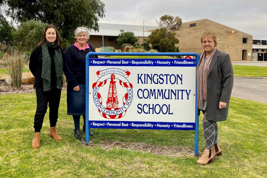 Three women stand smiling at the camera with a sign between them reading 'kingston community school' with buildings behind