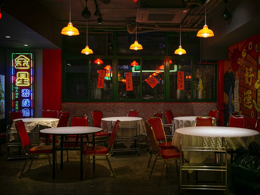 Empty red seats placed at tables covered in white table cloths below yellow lamps and neon signs
