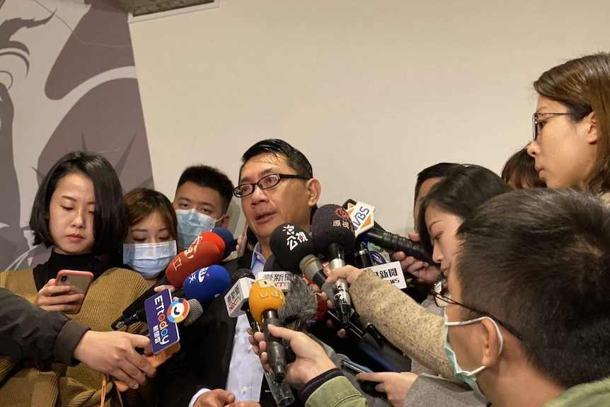 Vincent Hsu speaks to reporters who are holding several microphones near his face.