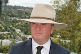 Barnaby Joyce wears an Akubra and speaks into a number of microphones in front of him.
