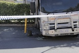 A truck with a broken window and damaged tyre.