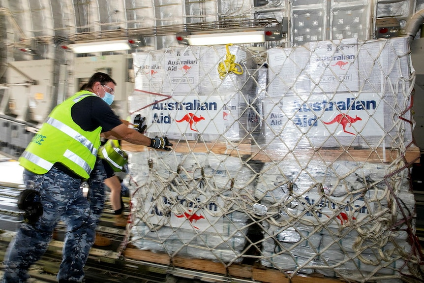 A member of the Australian Air Force loads aid packages onto a plane