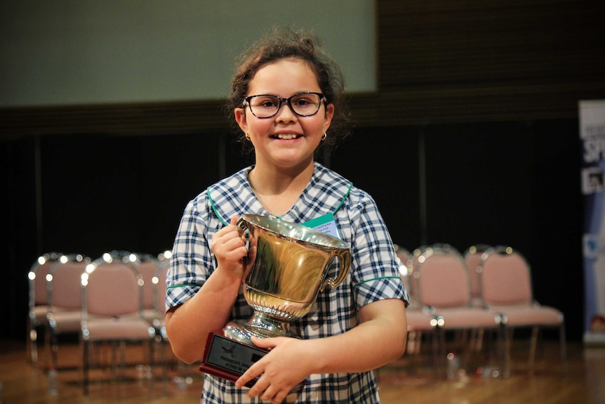 Nine-year-old Emilia McCarthy from Glenmore Park Public School smiling with her trophy.