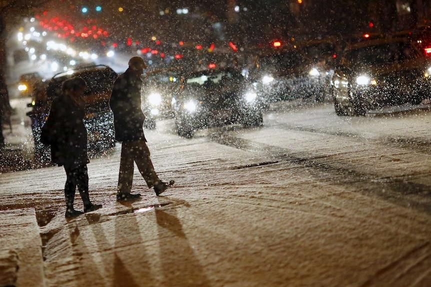 People cross a street as it snows in Washington.