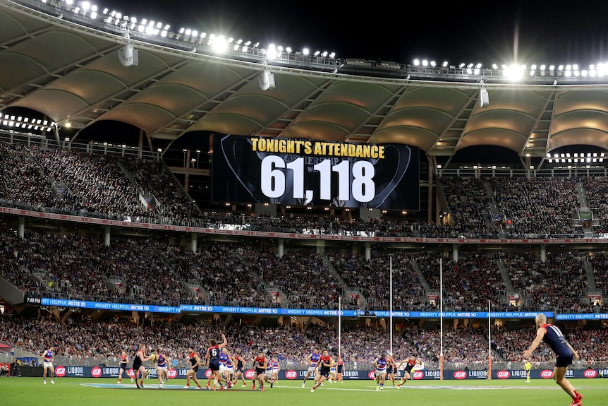 A sign in a packed stadium shows the attendance number