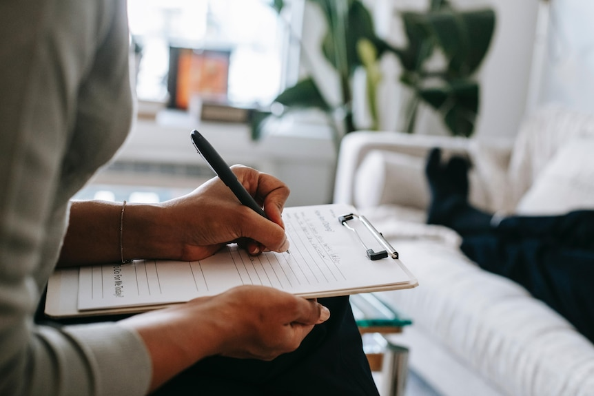 Psychologist's hands taking notes on a notepad