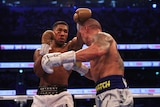 Anthony Joshua, with a damaged eye, punches over the head of Olaksandr Usyk