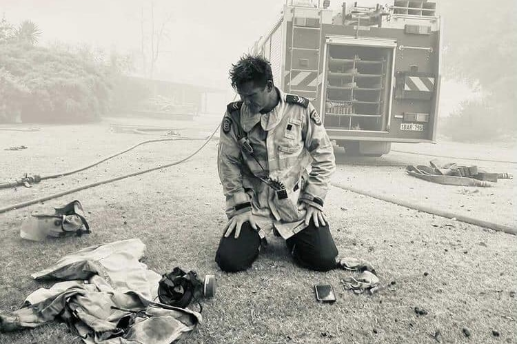 A firefighter kneels at the back of a fire truck, a respirator in front of him.