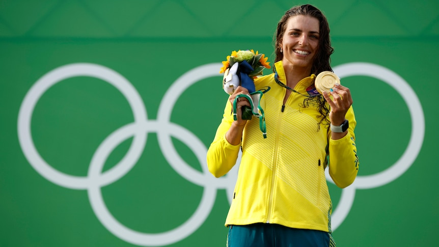An Australian female kayaker stands with her Olympic gold medal on the podium.