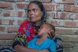 A Rohingya woman holds her emaciated child as she sits in the dirt.