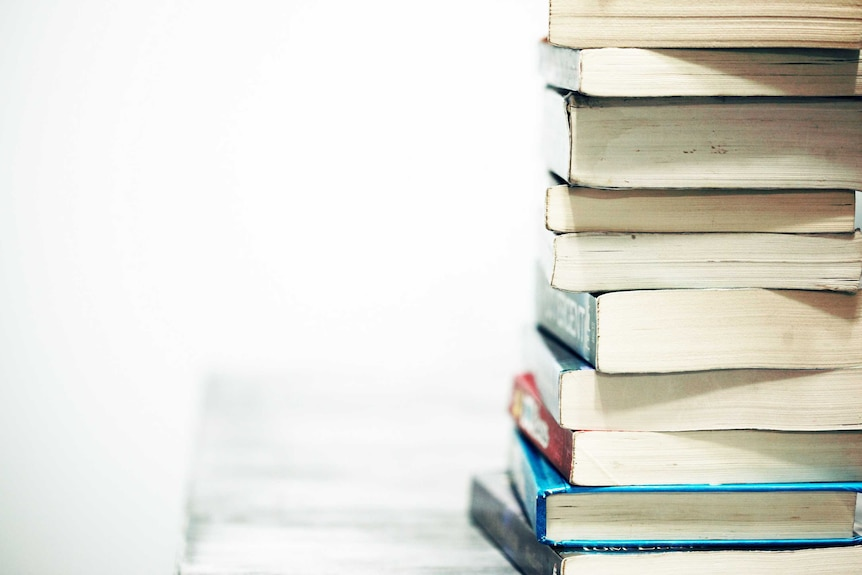 A pile of books sits on a desk to depict the need to upskill before a career change.