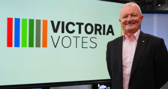 Antony Green stands in front of a screen which displays a Victoria Votes logo.