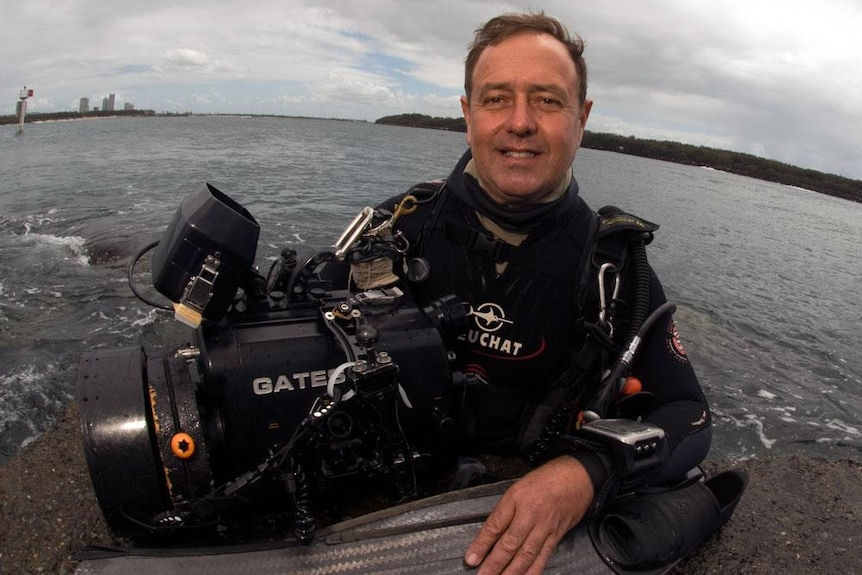 Diver Ian Banks in scuba gear with an underwater camera.