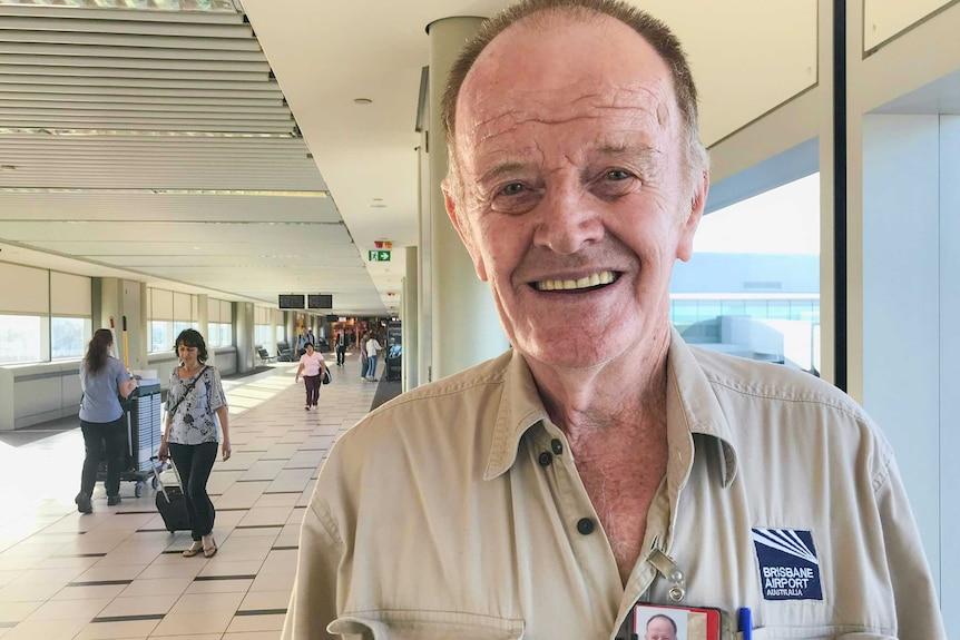 Man standing in an airport smiling.