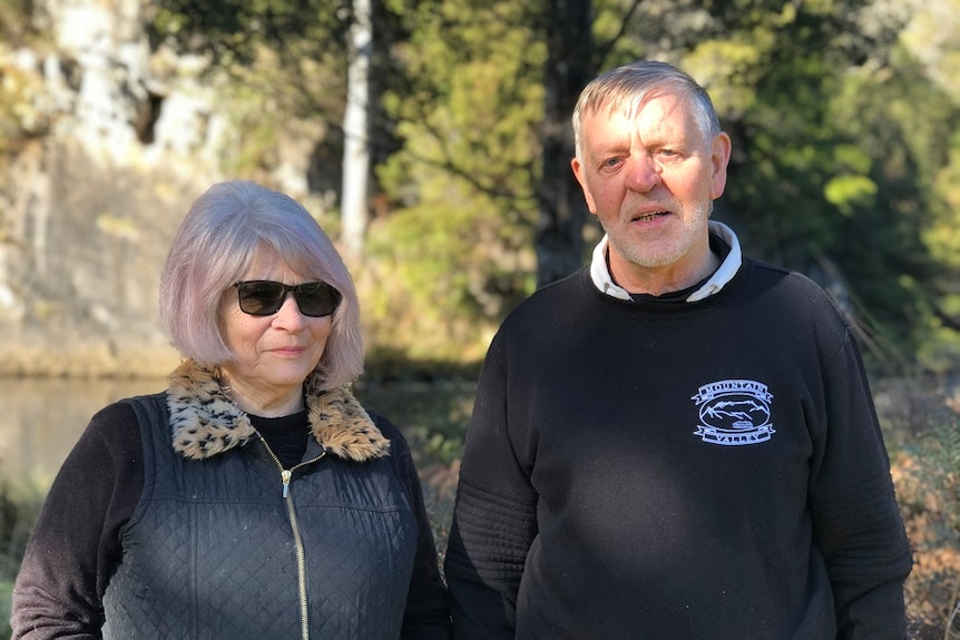 Tasmanian couple Pat and Len Doherty who own an accommodation business standing together with trees in the background
