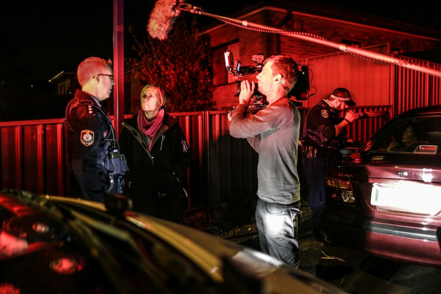 Night shot cameraman filming Ferguson interviewing policeman outside house with red eerie light from police sirens.