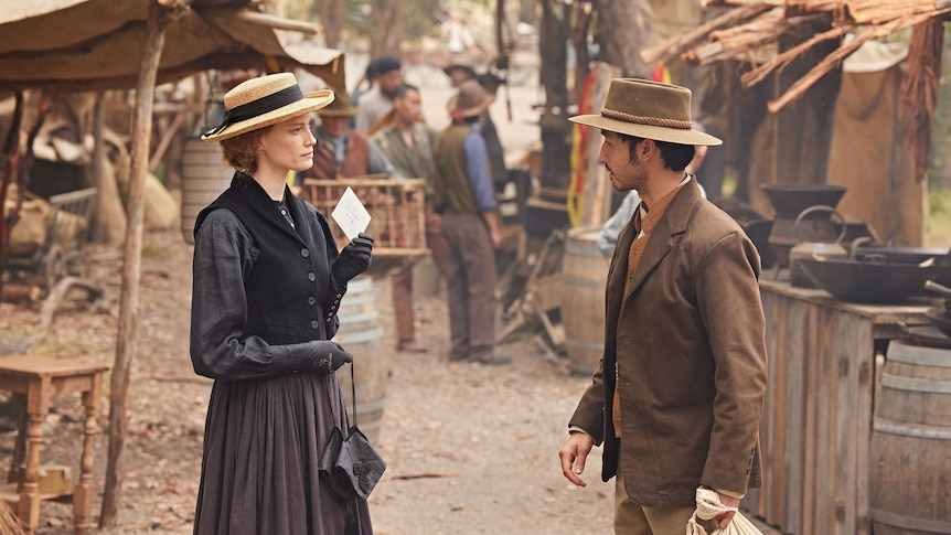 A woman and a man talk in a shanty town dressed in 1850s garb.