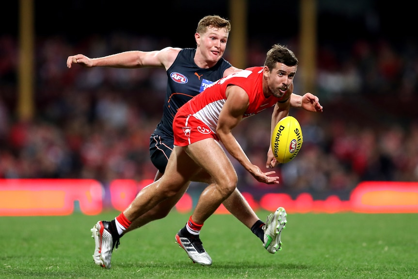 A Sydney Swans AFL player handballs in front of a GWS Giants opponent.