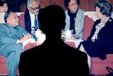A man's shadow falls on a photo of Deng Xiaoping sitting opposite Margaret Thatcher in a meeting.