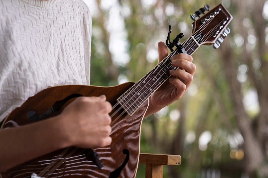 person sitting playing mandolin, close view of hands and fingers on instrument