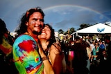 A grinning man and woman in bright clothes hug beneath a rainbow amid a crowd