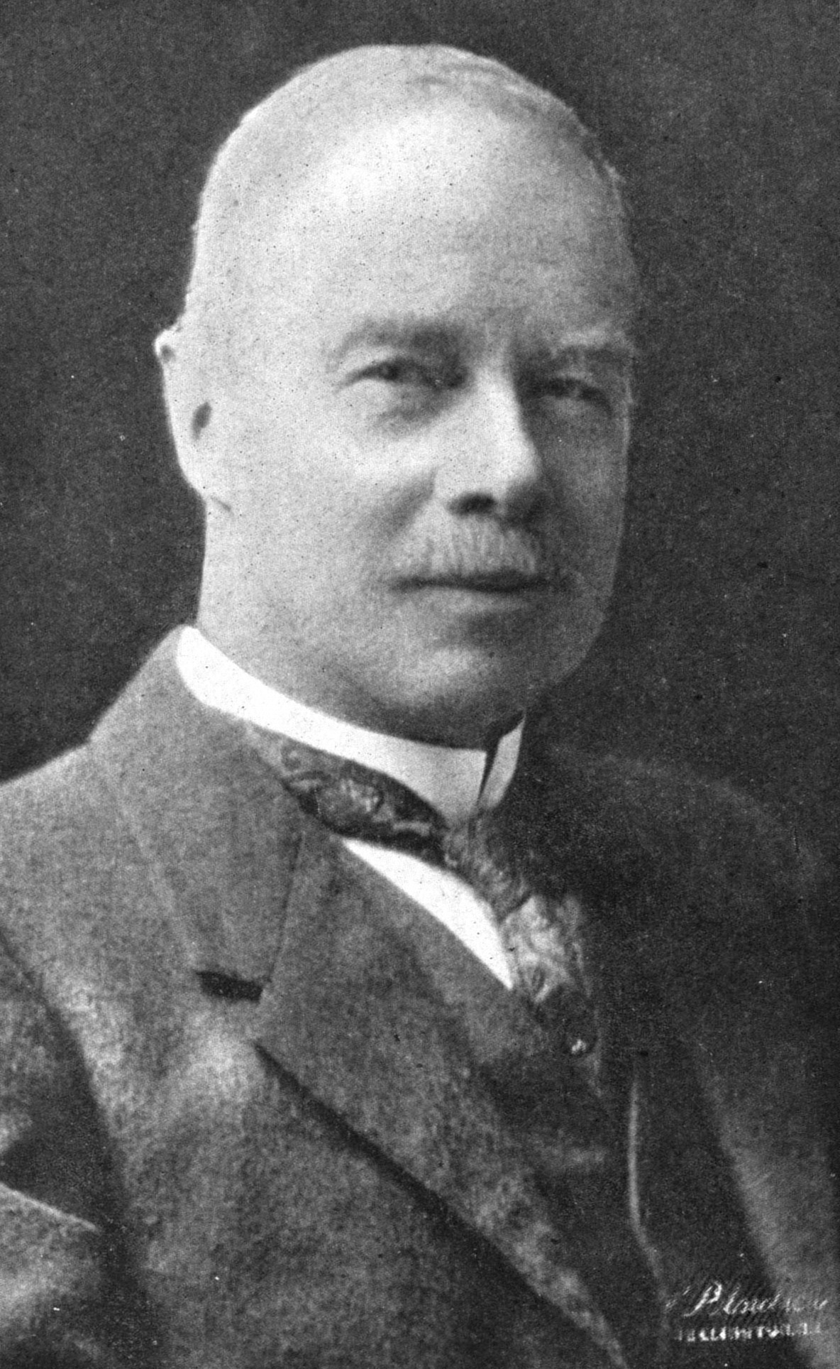 A black and white photo of a bald white man with a mustache
