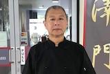 Charlie Men stands outside his restaurant.