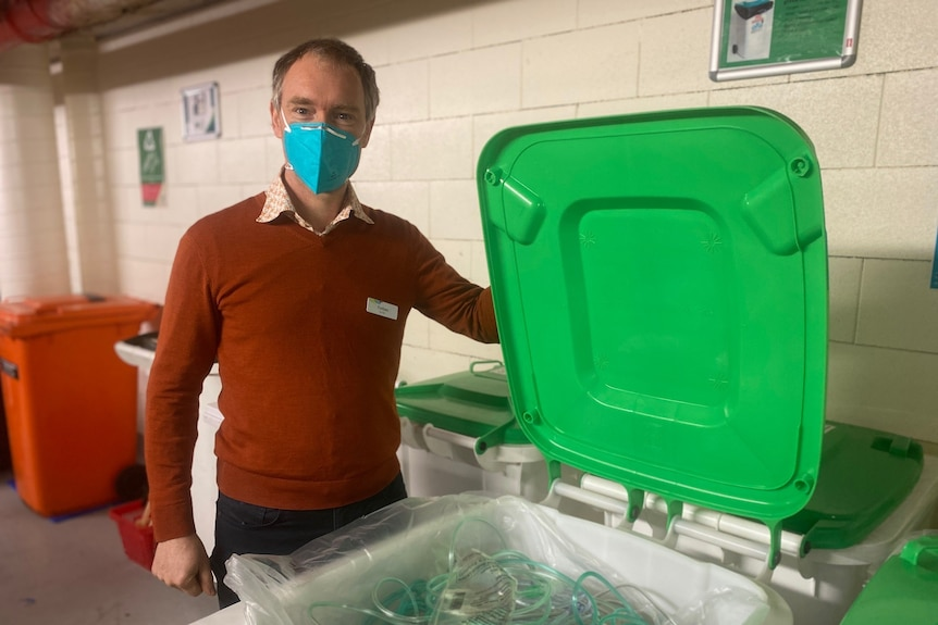 A man in a brown sweater opens a green bin with a mask on.