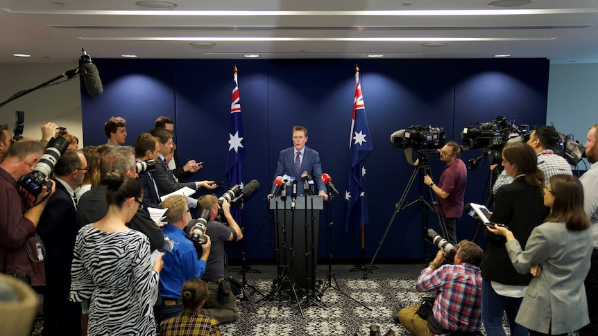 A man at a podium with microphones surrounded by journalists