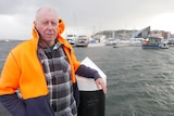 An older man in a hi-vis jacket standing on a pier in front of a hostile-looking sea.