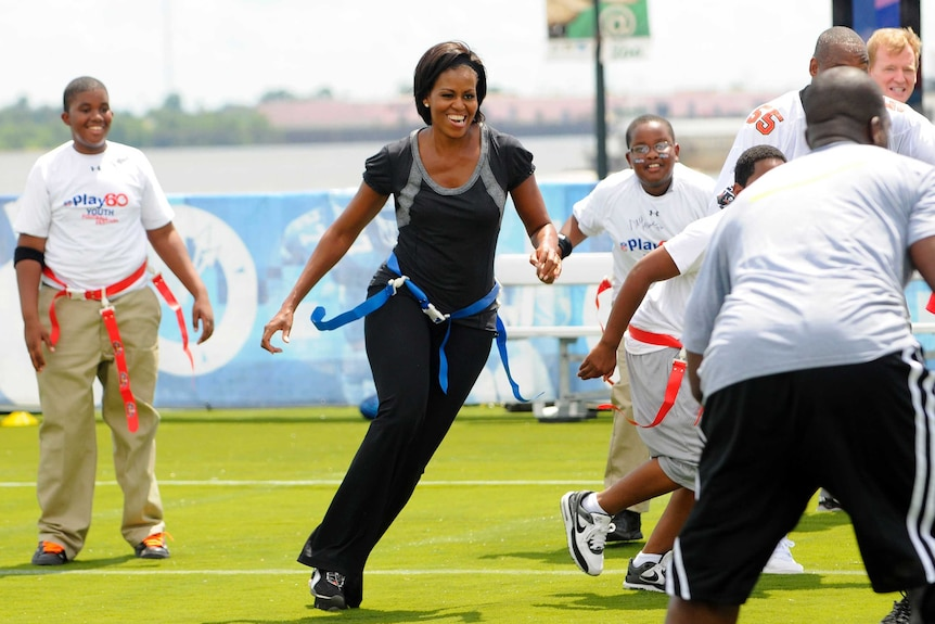 Michelle Obama jogs with children at Orr Elementary School