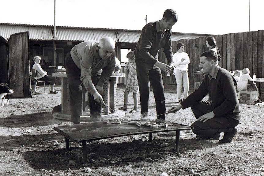 A black and white photograph of men tending to a BBQ on a metal plate on the ground.