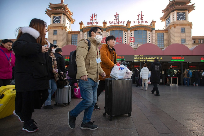 A traveller wears a face mask as he walks outside of the Beijing Railway Station with a crowd of people.