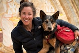 Adventurer Lucy Barnard smiling and dog Wombat looking at the camera holding an Ecuador sign