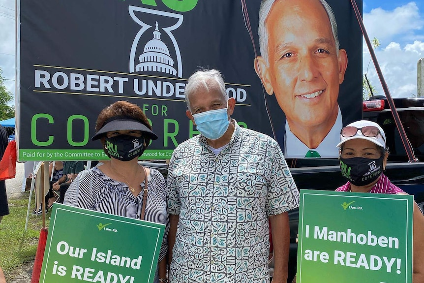 Guam politician Robert Underwood campaigns on the island. He is standing in front of his billboard alongside supporters