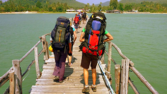 Backpackers walking down a jetty over some water.