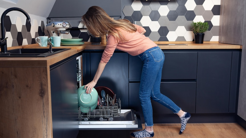 Woman stacking the dishwasher in her kitchen in a story about things you can dishwash besides dishes.