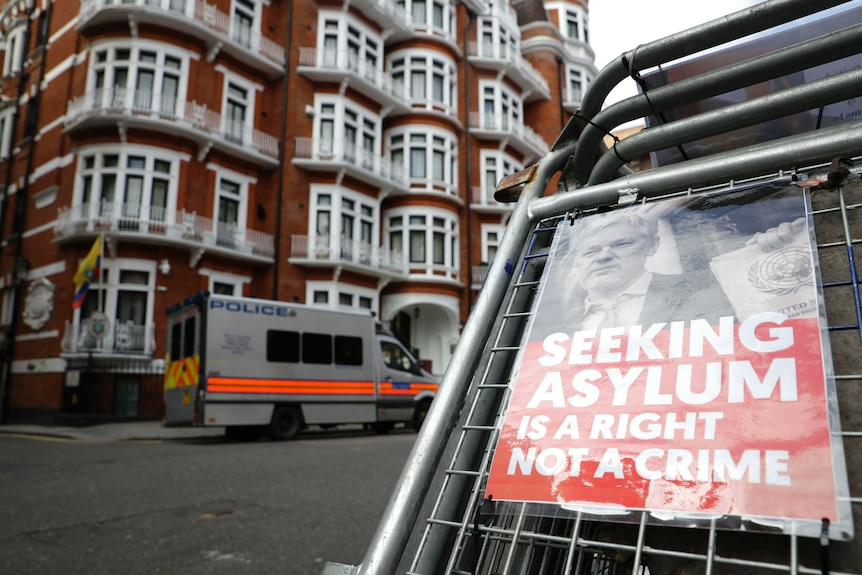 "A poster saying ""Seeking asylum is a right not a crime"" is attached to a barrier across from the Ecuadorian Embassy in London."